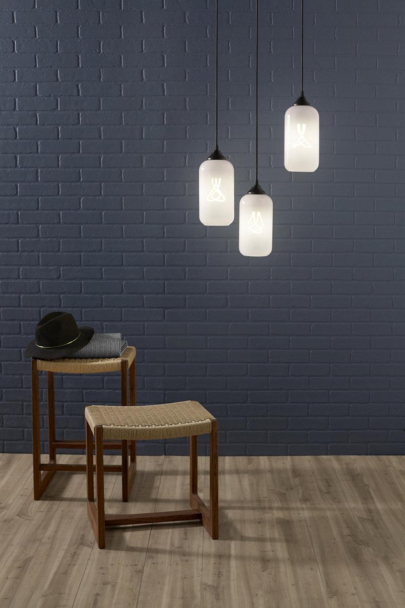 white glass pendant lights against blue brick wall