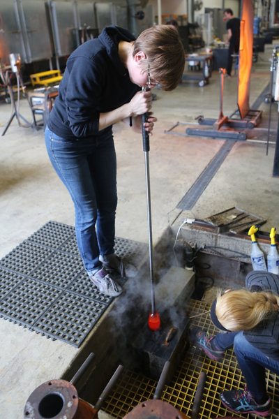 Andrea blowing hot glass into a mold