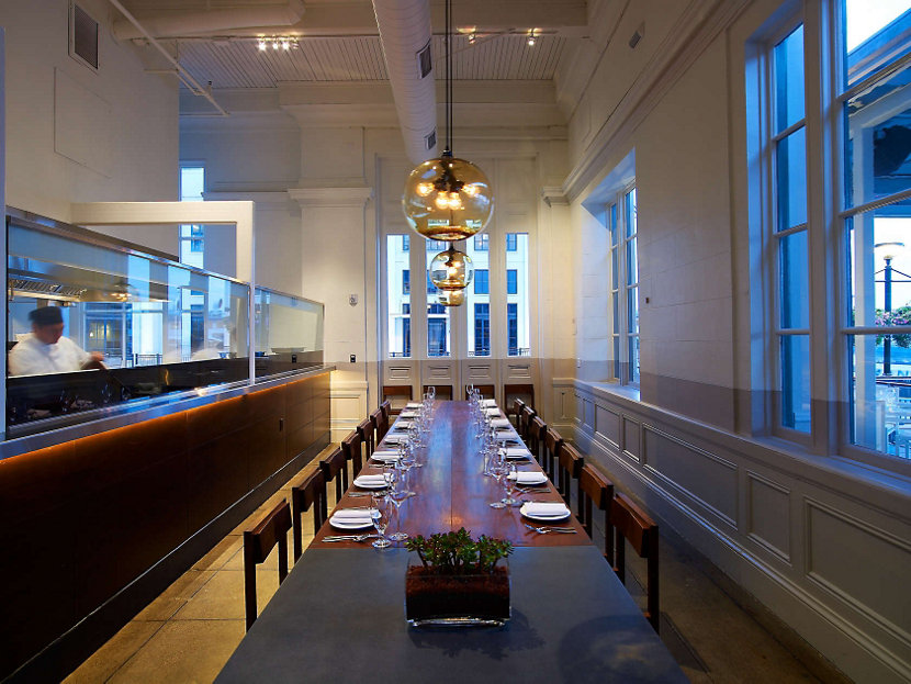 large glass pendant lights above private dining room table