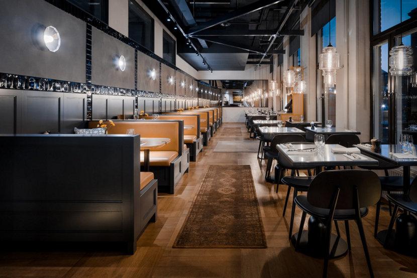 Guests Enjoy Meal Under Modern Restaurant Pendant Lighting