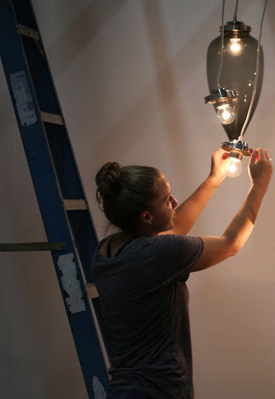 Niche marketing team member Britney installing lights for a photo shoot
