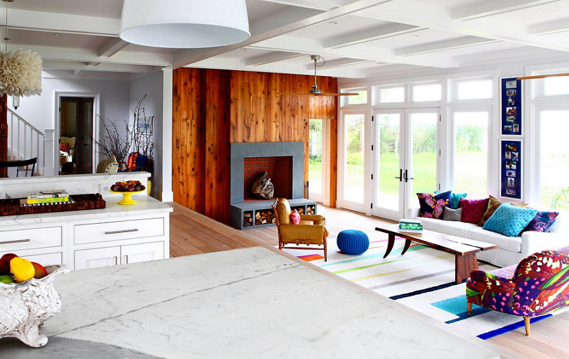 bare wood fireplace and modern pillows and furniture in beach home